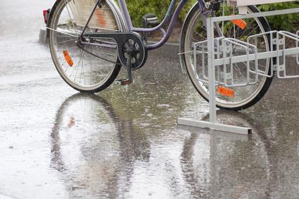 Regennasse Straße und ein abgestelltes Fahrrad