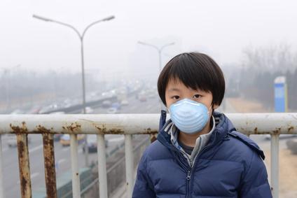 Junge mit Atemmaske vor Stadtautobahn in China