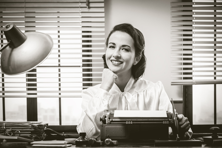 1950s style secretary working at office desk and smiling with hand on chin | Blogger