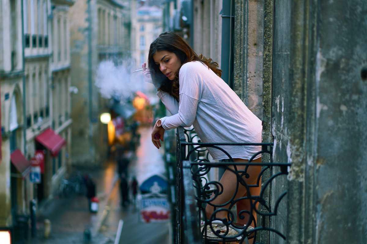 Frau auf Balkon in Frankreich